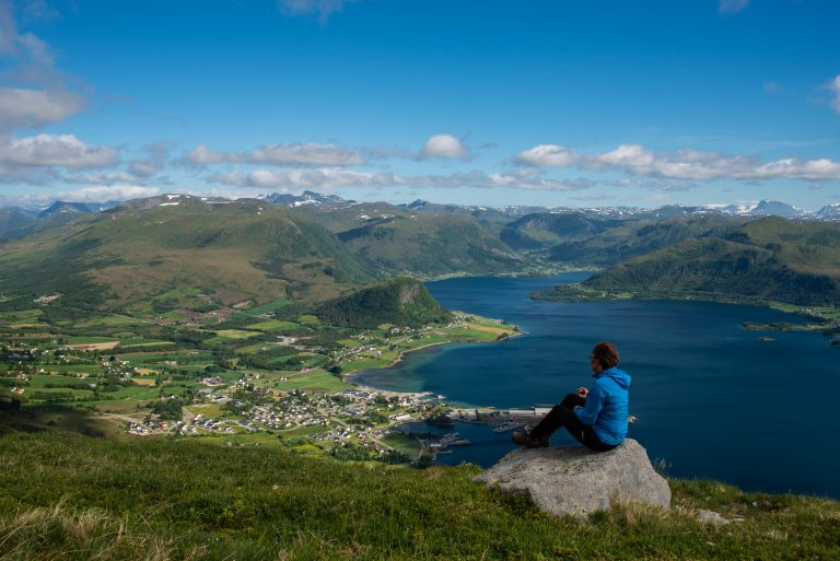 person sitting on rock looking out towards the fjords