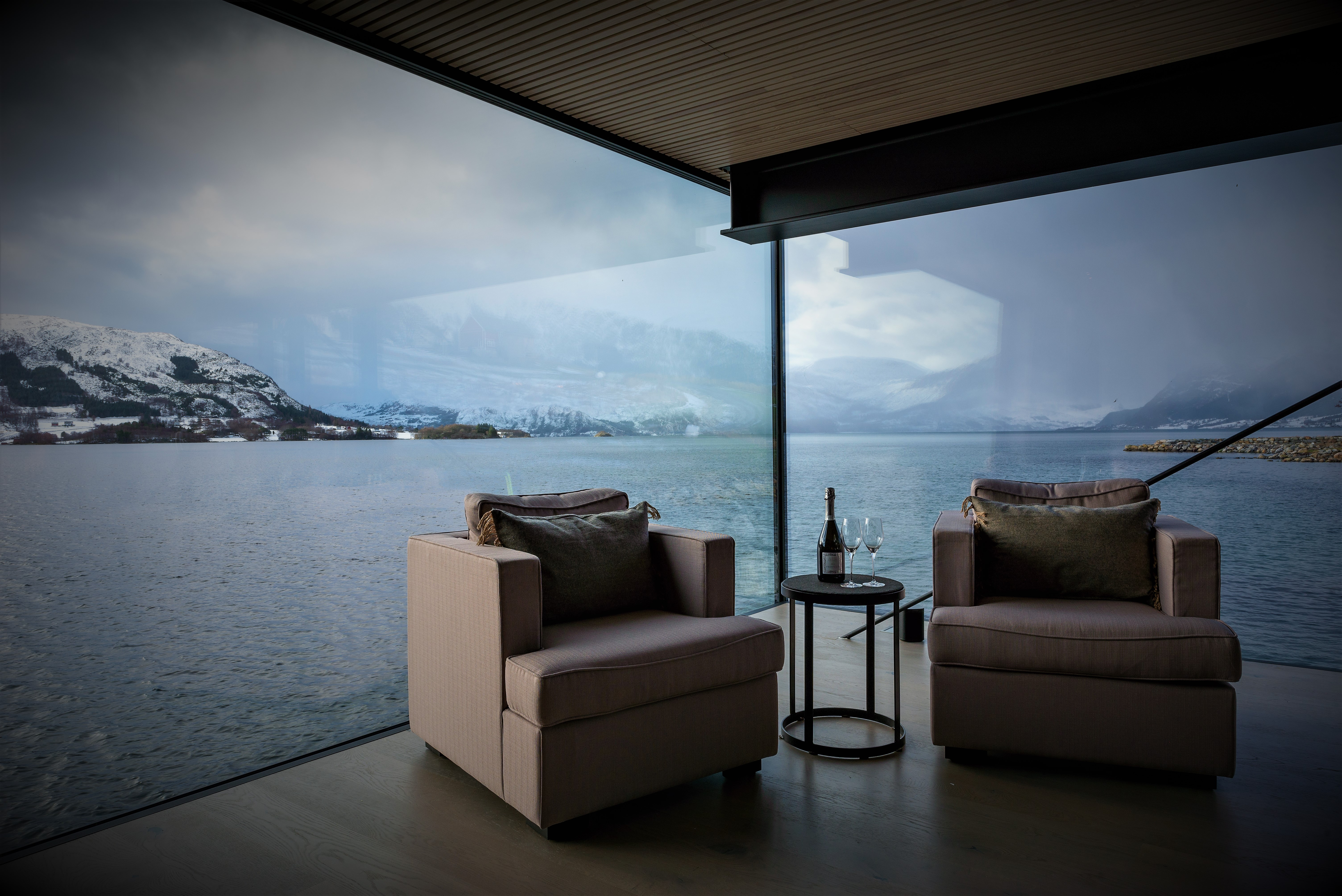 two chairs in front of window, fjord in the background